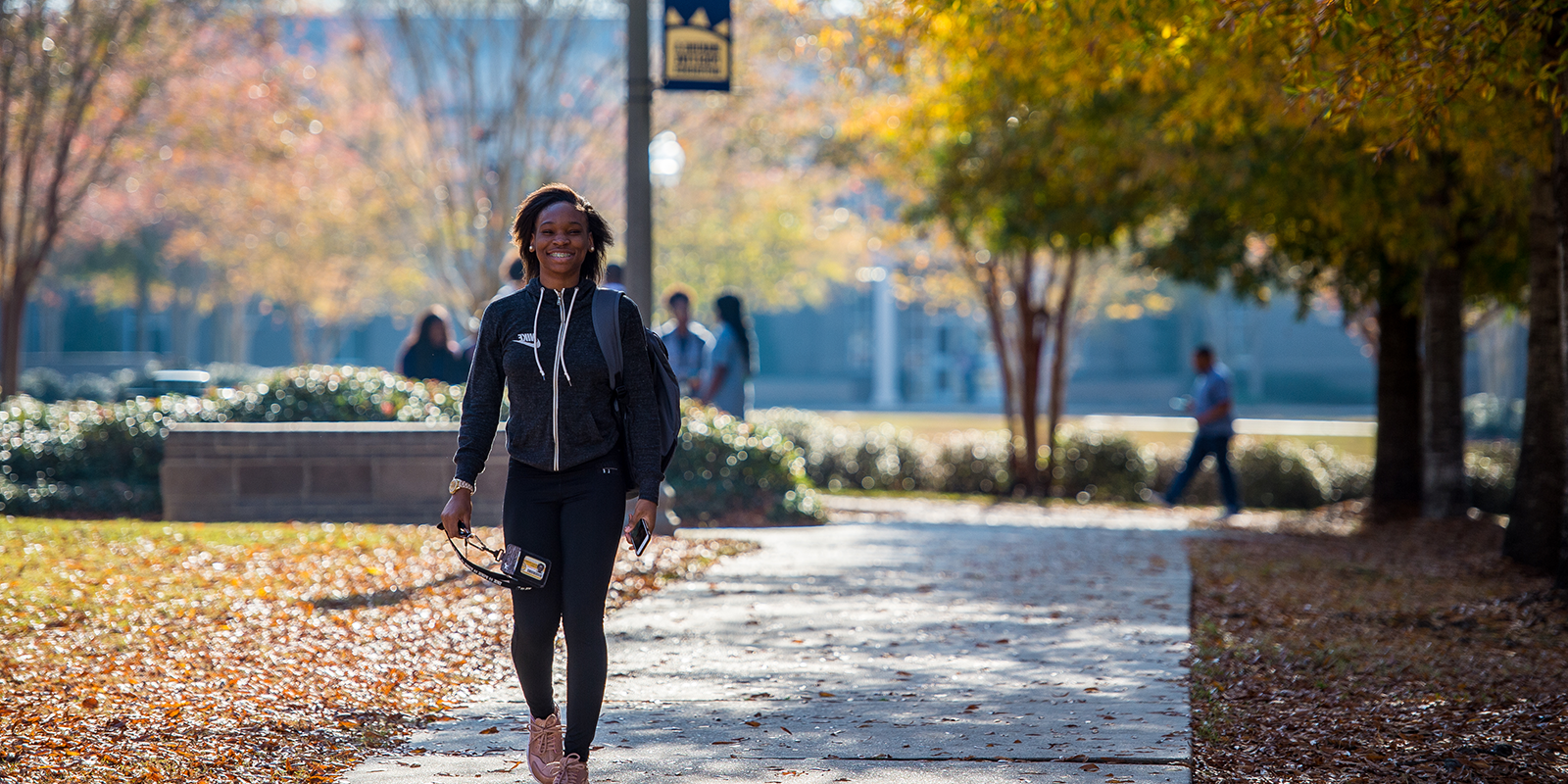 Student walking on the MGCCC campus smiling at camera